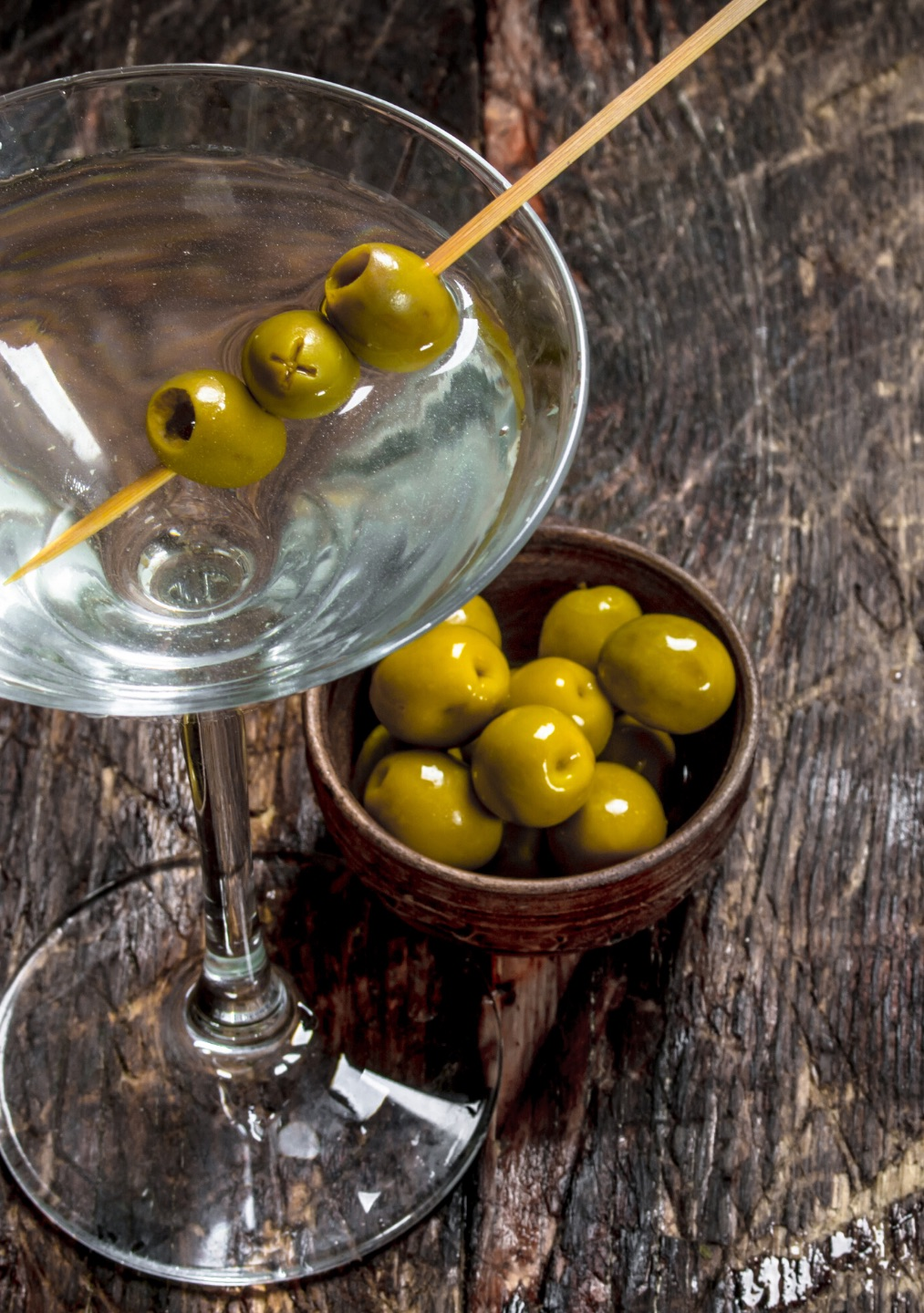 A Martini cocktail with three olives