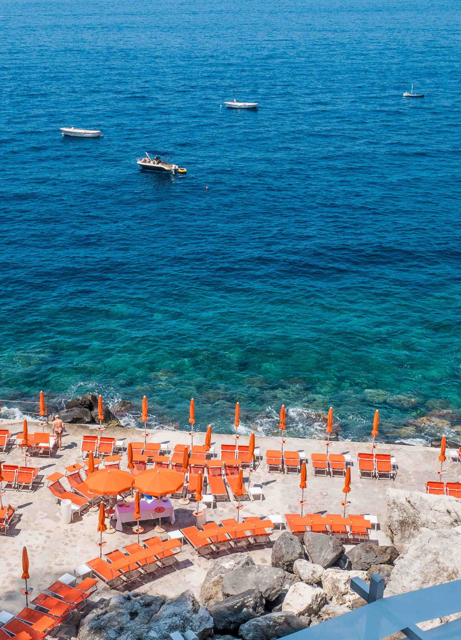 Beach with sunbeds at Praiano cliffs in the Amalfi coast, Italy.