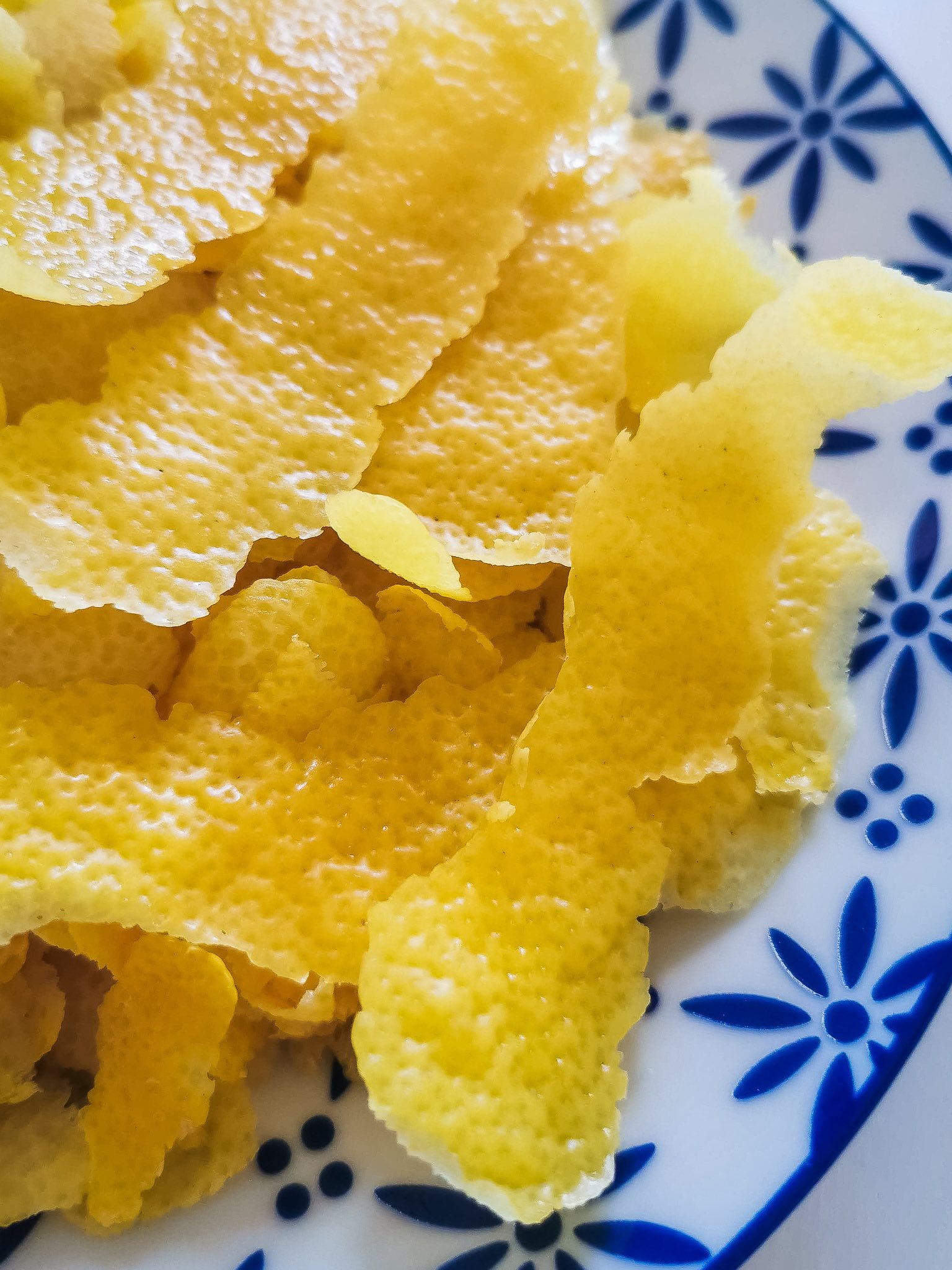 To make limoncello at home, peel the lemons making sure to avoid the white pith