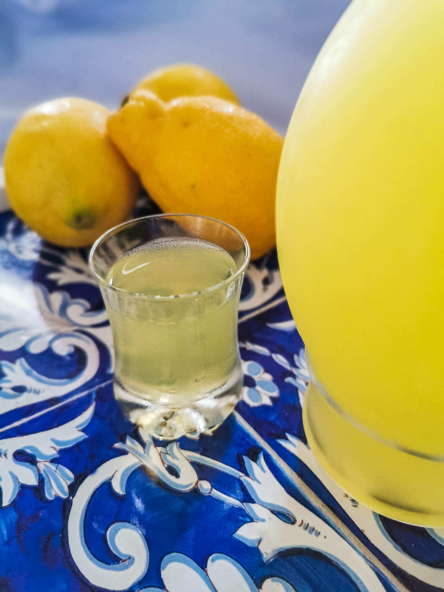 A bottle of homemade limoncello on a white and bue tray with a small glass filled with lemon liqueur and three lemons