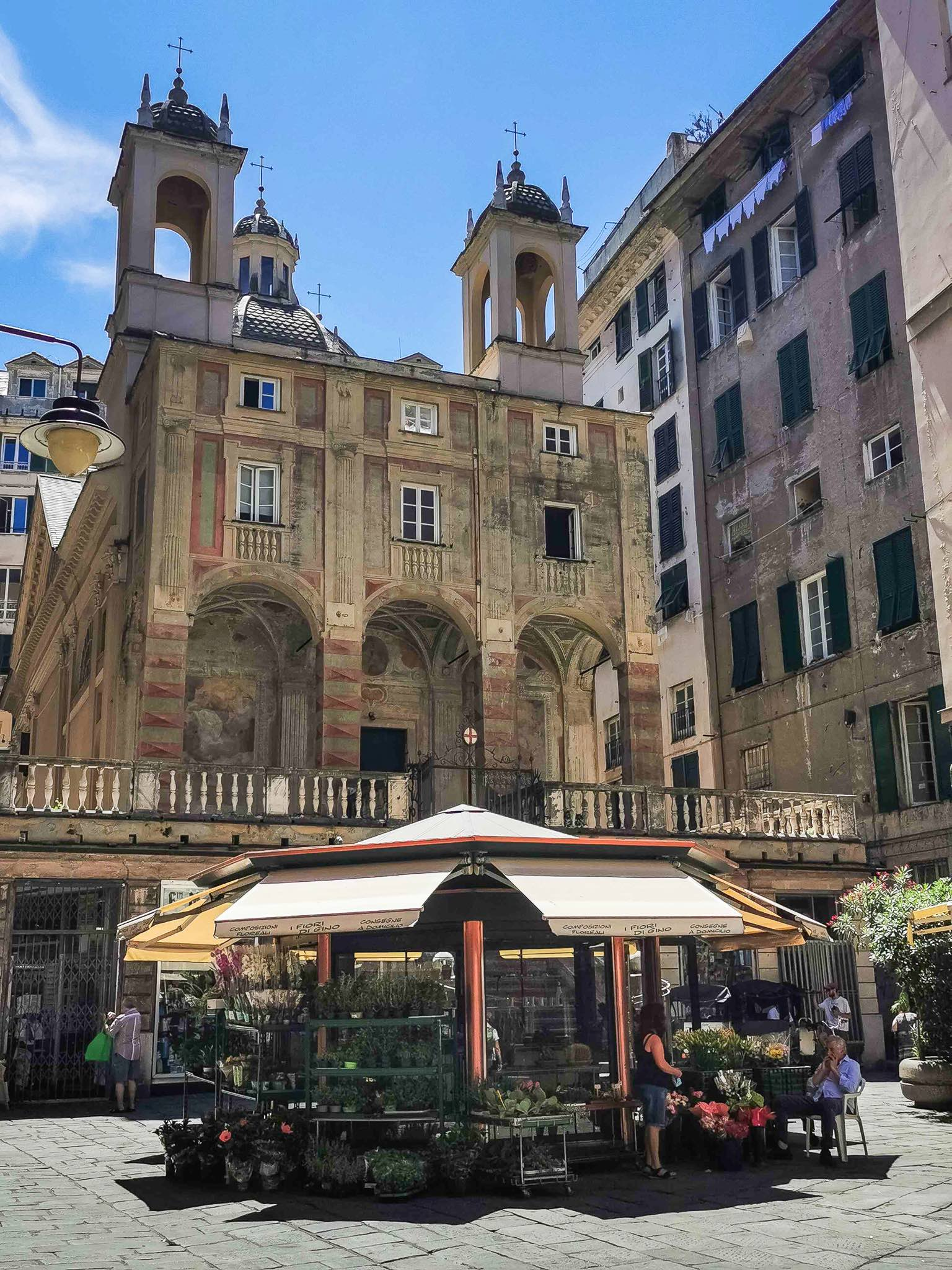 Piazza Banchi in Genoa with a flower kiosk and the Church of San Pietro in Banchi