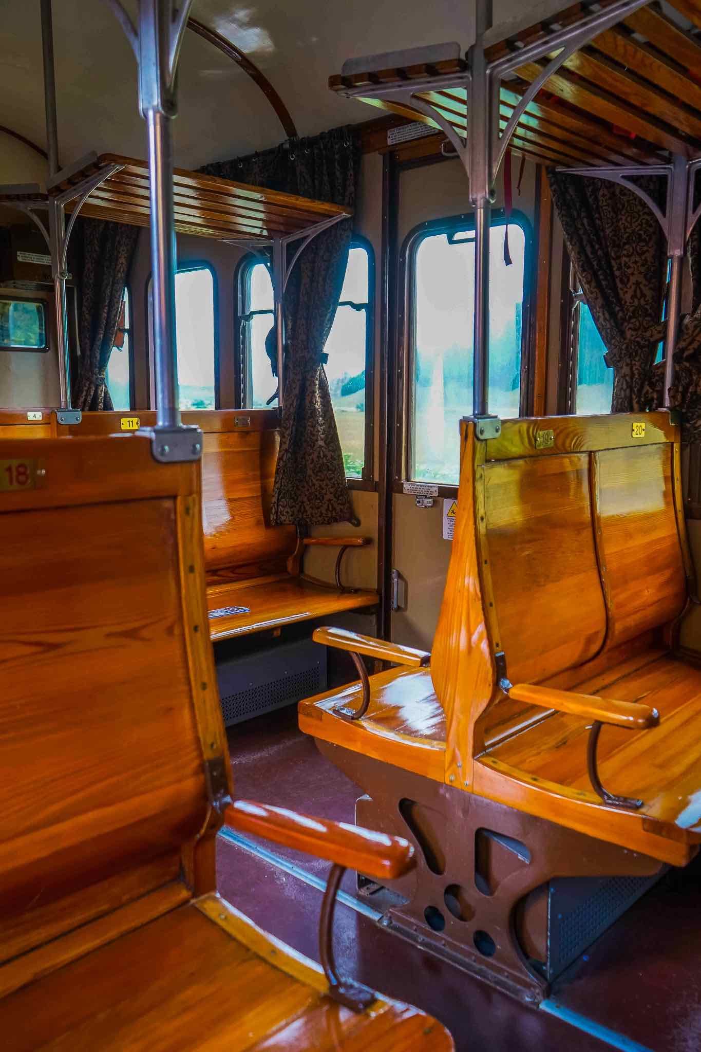 The original wooden benches inside one of the vintage carriages of the Italian Trans-Siberian railway
