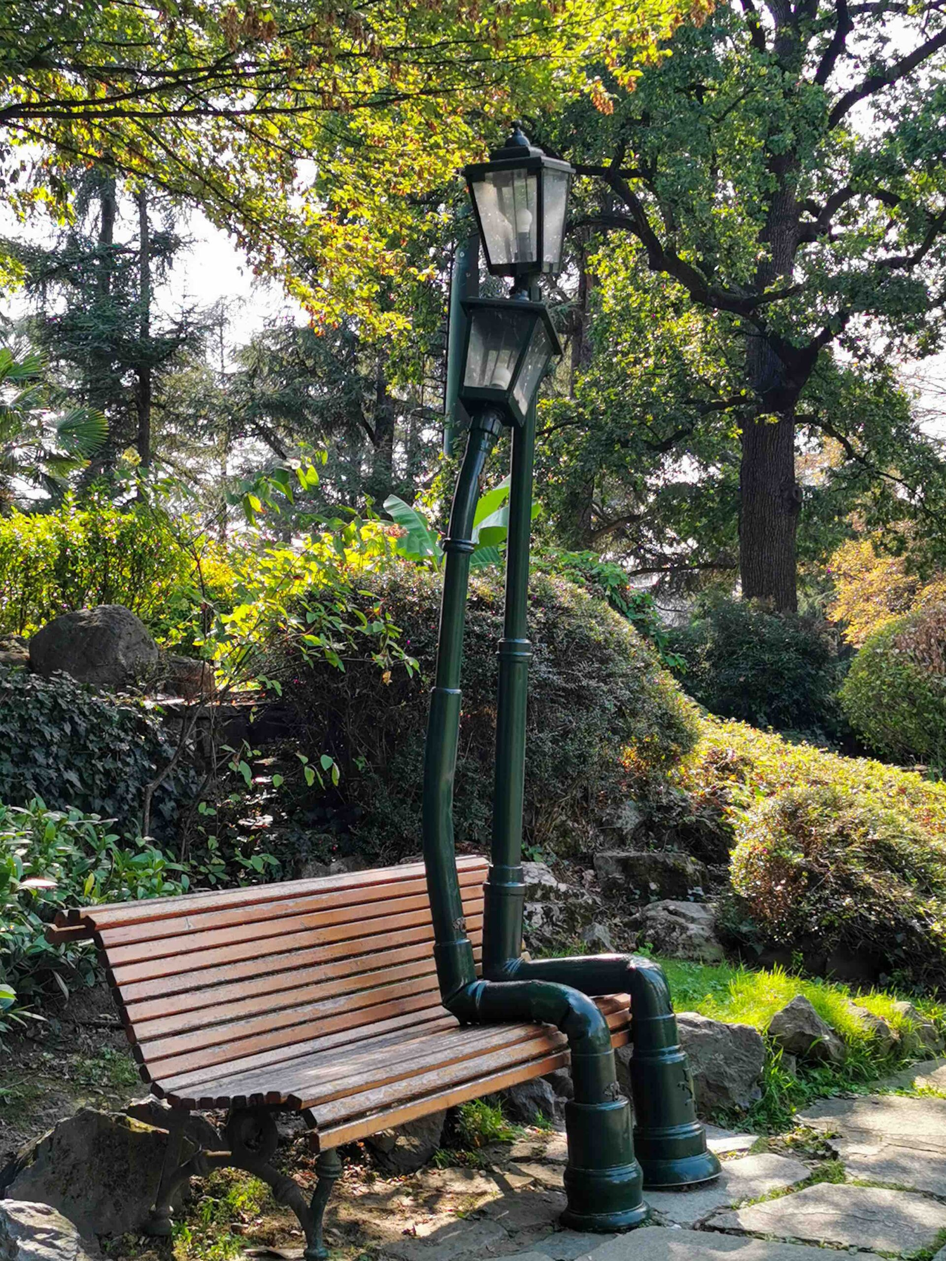 The romantic bench with two street lamps hugging each other inside the Valentino Park's rock garden in Turin
