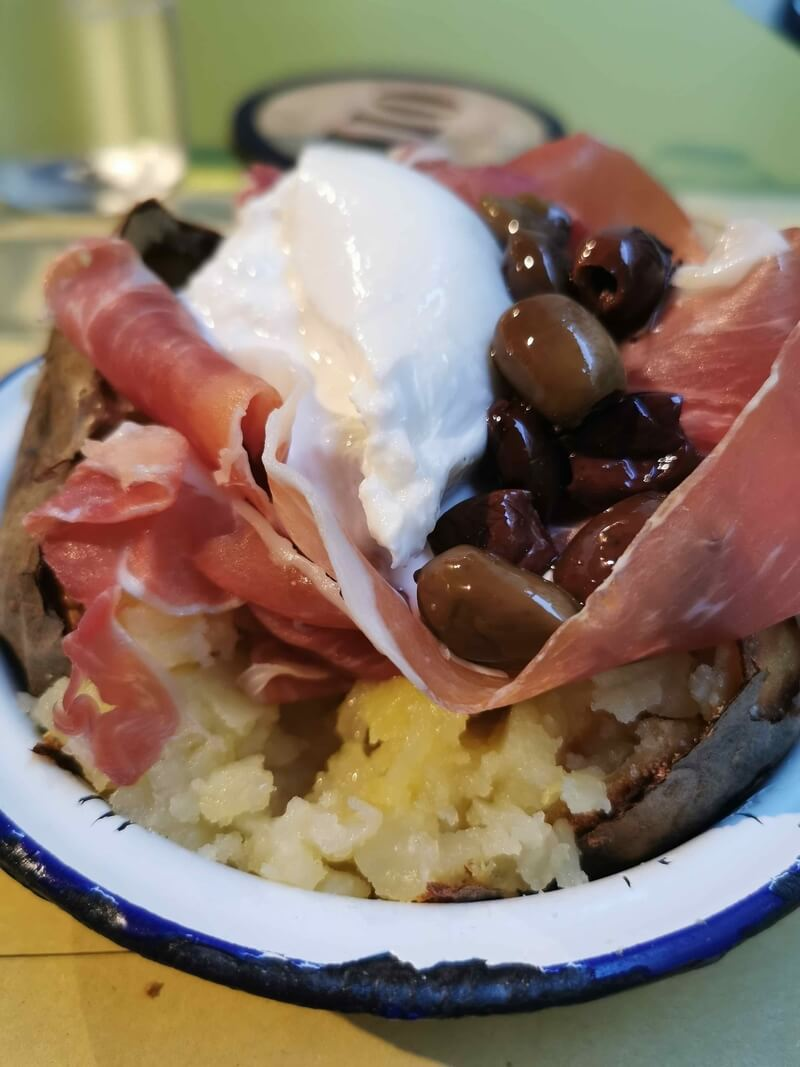 a jacket potato filled with burrata cheese, Parma ham and Taggiasca olives