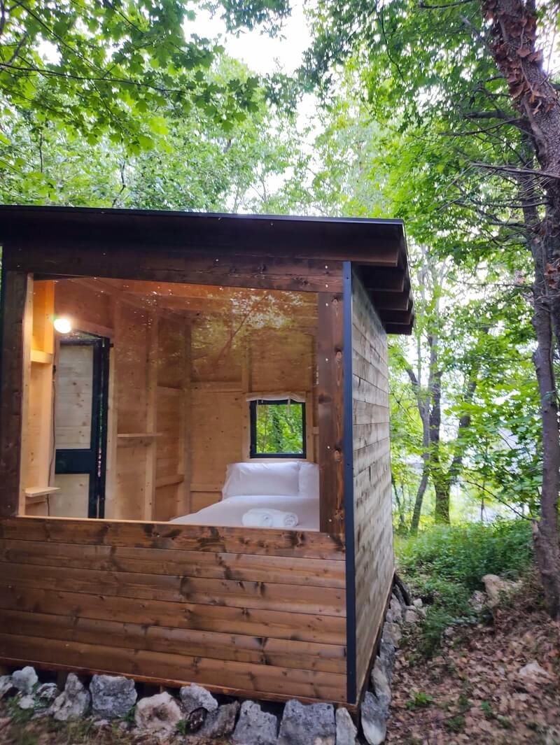 A wooden cabin with a big window overlooking a forest in the Majella National Park