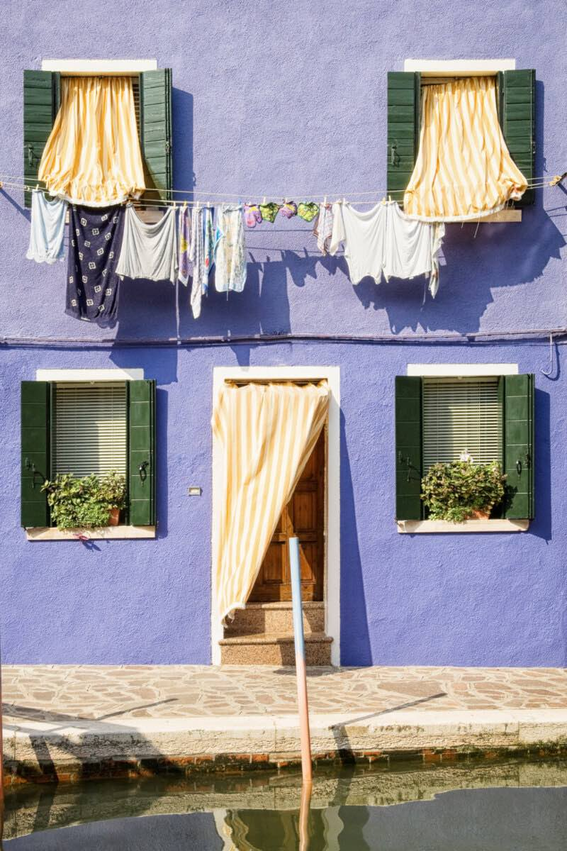 A house in Burano with purple facade and white and yellow curtains