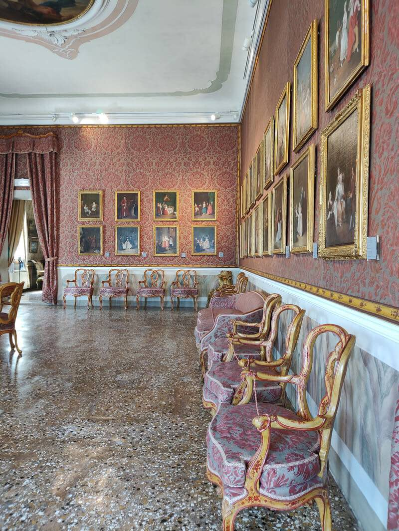 The Longhi Room inside Ca' Rezzonico Museum in Venice, with embroidered wallpaper and a series of small paintings in their original gilded frames.