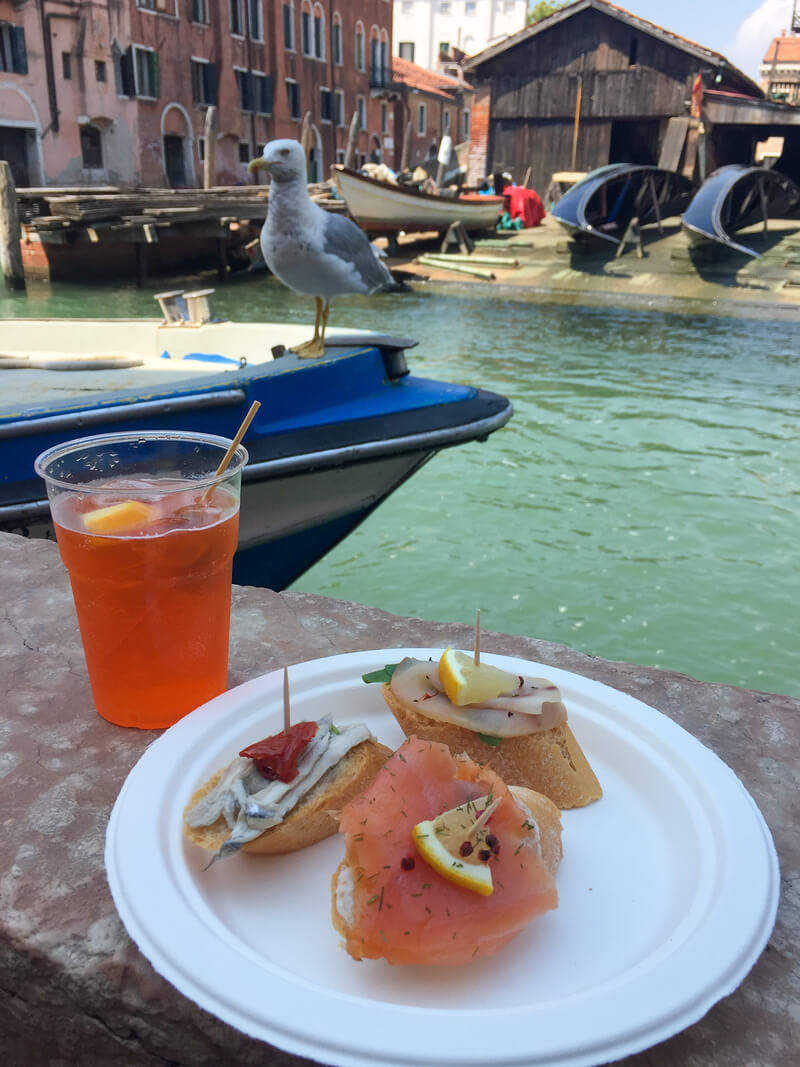 A plastic plate with three cicchetti and a glass of spritz by the canal, with a seagull in the background