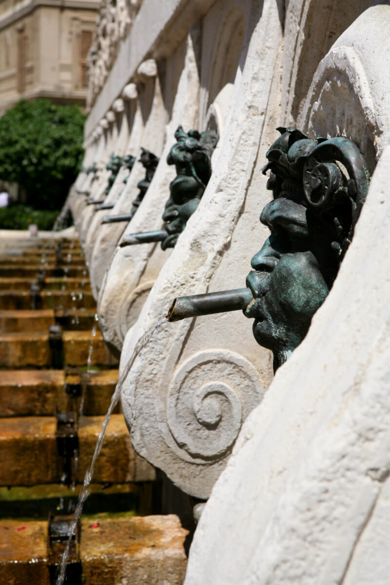 Water spouting from one of the bronze masks of the Calamo Fountain in Ancona