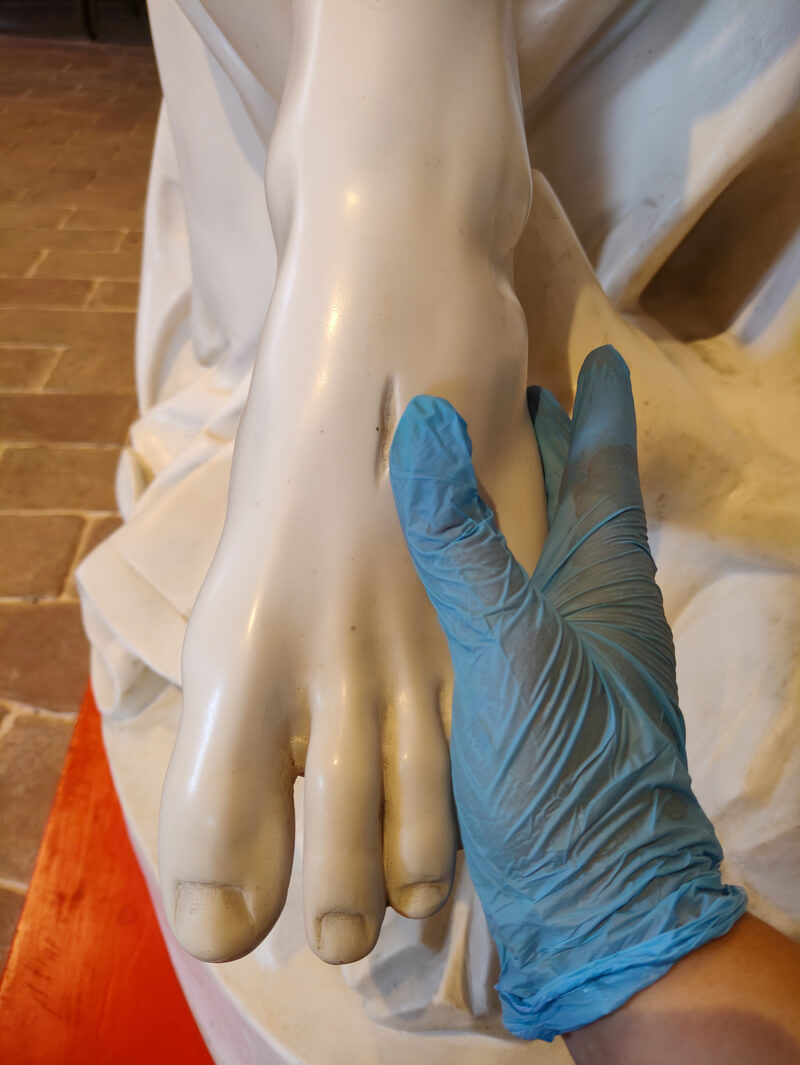 A hand in a blue glove touching the wound in Jesus' foot in Michelangelo's Pietà