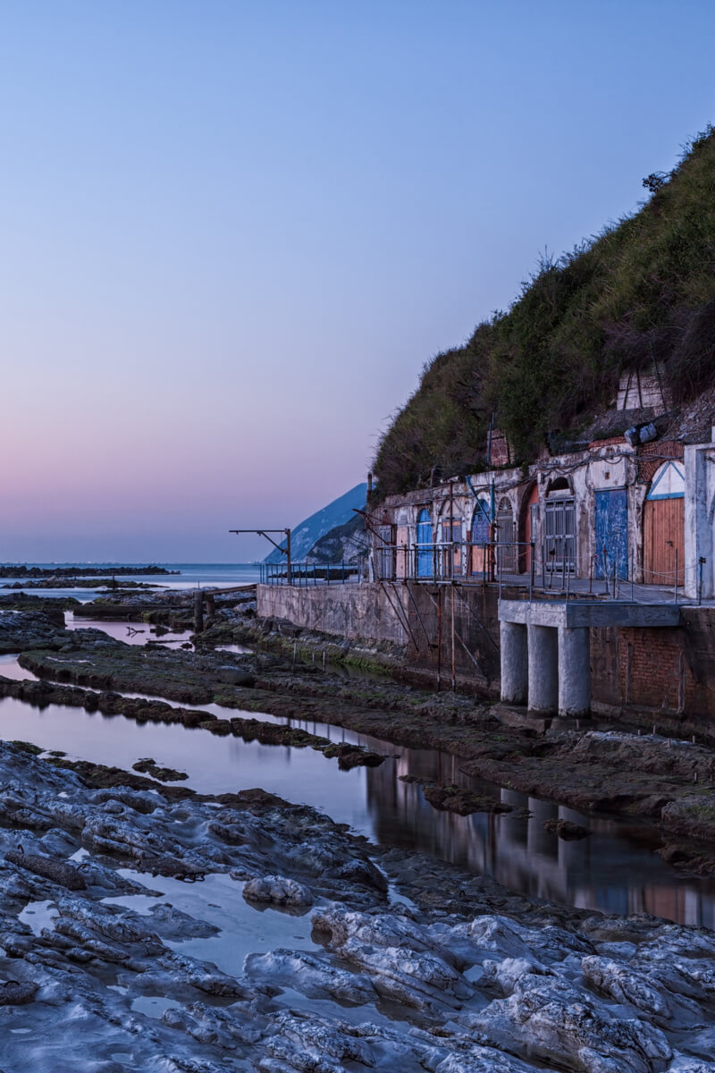 The colourful beach sheds carved out of the rock at Ancona's Passetto beach